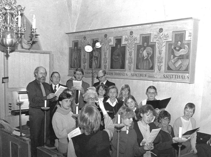 D. Varnhems kyrkokör sjunger i Norra Lundby kyrka. Fr v längst bak - strikt rad för rad från vänster till höger; 4:e & sista raden; Bror Antbäck, Allan Häggstam, Göran Berg och Nils Lann; 3:e raden; Eva Bosovic (skymd), Monica Johansson och Kerstin Lidberg; 2:a raden; Eva Skogsberg, Ingrid Sjöberg, Ulla Söderlund, (?) och Margareta Karlsson; 1:a raden; Margareta Murmylo (dirigent), Christina Andersson, Cecelia Söderberg, Ingrid Häggstam och Berit Karlsson. Insatt av Kent Friman, 2014-02-27.
