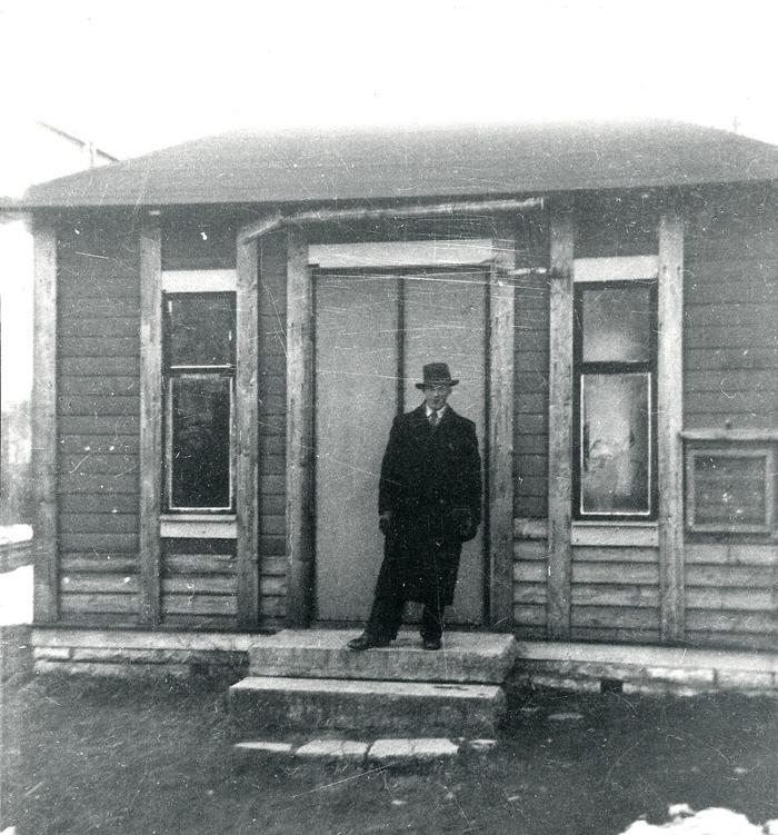 """A. 26 (1) (men annan kopiering!) Vid samma fototillfälle 1937 poserar sedan Karl Holmberg, Storekullen framför byggnaden som just det årtiondet hade förfallit en hel del. Karl Holmberg, Storekullen omkom i en el-olycka på Kyrkebo 1940. Bildtext ur arkivet: """"Ljungstorps anhalt. """"Väntsalen"""" vid Ljungstorps anhalt 1937. Byggnaden var ursprungligen tidningskiosk i Skövde kyrkpark och flyttades omkring 1914 (senast 1913 enl. tavlan) till Ljungstorp av disponent Grönvall och grosshandlare Högberg, vilken ägde ett par sommarställen i Ljungstorp. Byggnaden blev efter hand en träffpunkt för bygdens ungdom och kallades av folkhumorn för """"Lunsabingen"""". Smärre vandaliseringar och upprustningar avlöste varandra de sista åren före järnvägens nedläggning 1961."""" Foto Nils Lann (Text Västergötlands Museum - bildarkivet/bildnummer: A145127:6). Insatt av kent Friman, 2014-02-24. Läs mer på www.saj-banan.se!"""