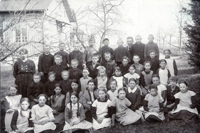 F. 0 (3) Finns i gul pärm. Elever hos Gabrielsson i Varnhem 1920. Övre raden från vänster; Mechtild Rosander, okänd, okänd, okänd, okänd, okänd, okänd, Håkan Gabrielsson, Erik Falk och okänd. // Andra raden uppifrån från vänster; Okänd, Okänd, Erik Holmberg, okänd, okänd, okänd, okänd och Herta Jansson (Lind). // Tredje raden uppifrån från vänster - sittande; Pojke okänd, okänd, Sven Gustavsson, okänd, Karin Karlsson, okänd, Violet Bast, Märta Holmberg, okänd och okänd. // Fjärde raden uppifrån från vänster; Flicka längst till vänster, okänd, en bit in i raden, Nancy Fredén, Anna Haakon, okänd, okänd, okänd, Elsa Gustavsson, Elsa Stig och Beth Rosander. // Femte raden uppifrån (främre sittande) ; Okänd, okänd, Helga Lindal (Johansson), okänd, Ingrid Blomkvist, okänd och okänd. Insatt av Kent Friman, 2014-03-03.