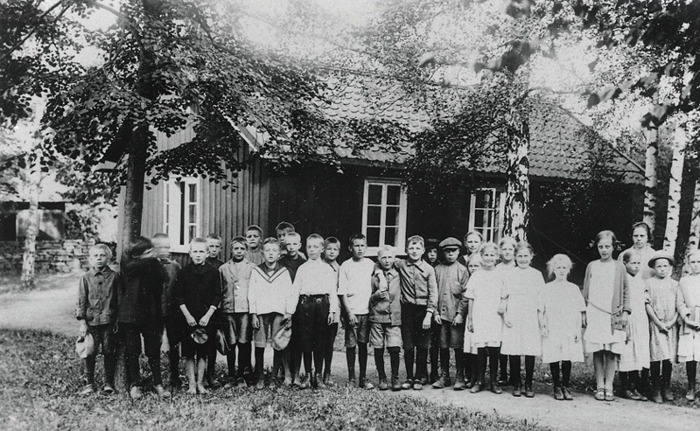 """F. 15 Skolfoto från Varnhem 1925, den så kallade """"Mellanskolan"""" som låg i kyrkeparken i det gamla """"Klosterbohlet"""". Lärarinna; Alice Mattson var extra ordinarie folkskollärare mellan 1924 och 1929, då hon bodde Folkskolan, Varnhem. Insatt av Kent Friman, 2014-03-03.  Lägg märke till bostadshuset på Kyrkogatan mitt emot, där Trumfa-Karlssons bodde strax före den här tiden. Han hyrde denna stuga som jordbruksarbetare för Trädgården mellan 1910 och 1918 under tiden de fem barnen med den 2:a hustrun föddes. Den låg vid Kyrkoallén i Varnhem. Här bodde också 'Ferma-Tilda' med sina söner under ett antal år."""