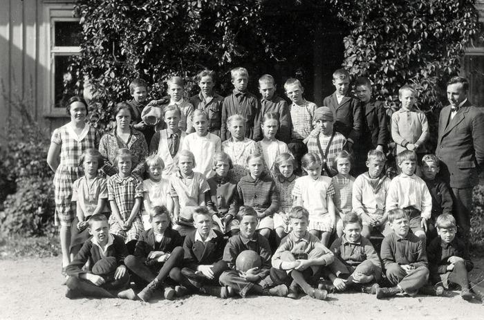 F. 13 (2) Varnhems Skola höstterminen 1928, klasserna 1-5. Lärarinnan Tyra Andersson till vänster och läraren Håkan Gabrielsson till höger. Vid hans fot, sittande Evald Friman och hans tvillingbror Egon Friman stående bakom honom. Insatt av Kent Friman, 2014-03-03.