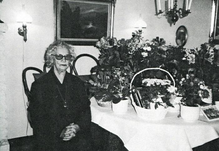 """G. 14 Endast digital bild! Edith Pettersson på sin 85-årsdag 1997 i Vallehemmet. Bild från Varnhemsbygden 1998. De byggde snart till en del för utvidgning av caféet mot öster, bakom kiosken på bilden. Några av de unga Varnhemsborna på den tiden samlade på trappan till Caféet med goda smörgåsar och annat gott annonserat på fönsterrutorna. Cloetta mjölkchoklad och Marabou mjölkchoklad fick båda plats med reklamskyltar på taket till kiosken. I bakre raden skall enligt dottern Roland Johansson finnas. Runhem var också plats för skolbespisning för Varnhemseleverna under 1960-talet med Edith Pettersson som matvärdinna. Bakom Runhem till höger skymtar dåvarande Församlingshemmet, som också var småskola för 1:a och 2:a klass under ett antal år. Därefter kommer ladugården för Trädgården med gavel mot landsvägen, som också var en av de byggnader som försvann i o m Varnhemsbranden 1979. Den är återuppbyggd för annat ändamål. Om någon vet vem som är vem på bilden - så hör gärna av er! <-- Till sidans topp! Edith Pettersson på sin 85-årsdag 1997 i Vallehemmet. Bild från Varnhemsbygden 1998 Edith Pettersson på sin 85-årsdag 1997 i Vallehemmet. Bild från Varnhemsbygden 1998 När Erik och Edith Pettersson kom till Runhem från Kålland utvecklades både Café - och kioskverksamhet. Där blev ett gott tillhåll för de som närmades sig tonåren, men också för dem som kommit upp i motoråldern. Edith kunde verkligen """"ta"""" ungdomarna på rätt sätt och de flesta kände sig som hemma. Hon anställde många ungdomar genom åren att arbeta både i Caféet och inte minst i kiosken. Kiosken hade sin höjdpunkt inte minst när Västgöta-Bengtsson kom med sina militärresor med hundratals värnpliktiga och befäl för Klosterguidning. Då skulle det gå snabbt och glassarna fick plockas från botten av frysen innan alla hade fått köpa sin. Puckstång 30 öre, God-ice 60 öre, Storstrut 1:25 och för 2:25 kunde man köpa en halvliter och den delades då i två delar och skedar lånades ut. Det gällde också för de kioskarbetande """
