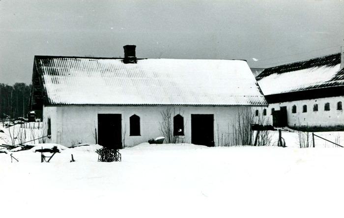 Bild från Carl Arvid Tell av Backa gårds Smedja som revs 1976 i samband med uppförande av ny bostad. Sättningar i grunden gjordde det omöjligt att hålla byggnaden i skick. Ett s k Gjuthus troligen byggt på 1880-talet. Gjuthus uppfördes med sand och kalk.  Vid mitten av 1800-talet blev ladugårdar och andra ekonomihus uppförda med en gjuten stomme av kalkbruk och sten mycket populära i hela Sverige. Senast användes det till smedja till vänster och snickeri till höger. Foto Krister Hallgard (bror till Ingrid Tell). Infört av Kent Friman efter Fotokväll, 2015-09-17