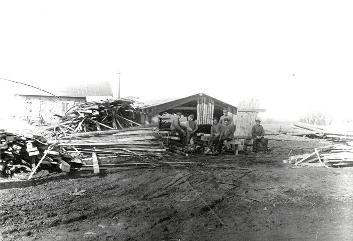 E. 12 a Arbete vid Tomtens sågverk framför smedjan 1920-tal. Bilden insatt av Kent Friman 2016-07-14