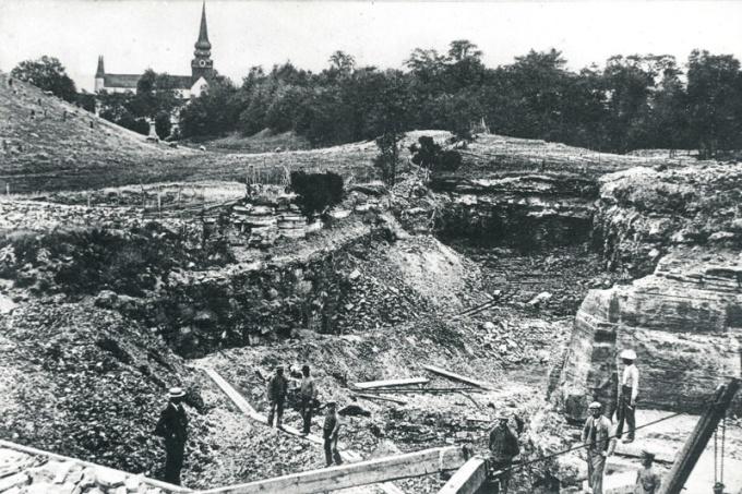 Från DigitalaArkivet: C. 15 (2) Ulunda kalkbrott, Varnhem, låg vid Hammaren. Bild troligt tidigt 1900-tal. Lägg märke till den lilla ugnen i backen utanför hägnaden till kalkbrottet mot kyrkan till. Insatt av Kent Friman, 204-02-26.