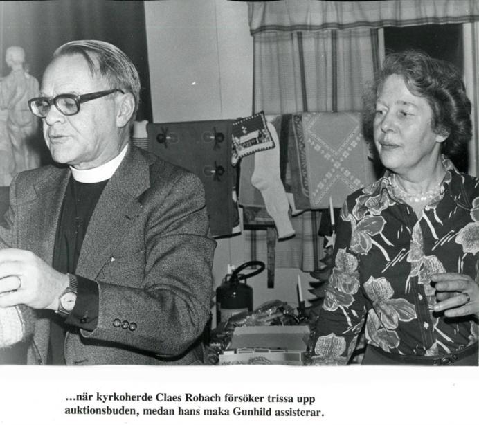 Kyrkoherden Claes Robach med assisterande maka Gunhild fungerar som auktionsutropare. Foto Bo Ramviken. Bild från Gudrun Ramviken, Sörgården, Varnhem, 2014.