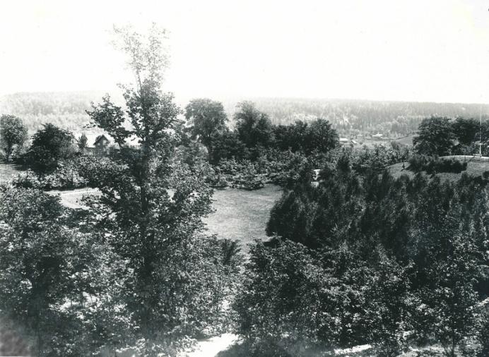 """Utsikt över kyrkparken 1904. Bilden tagen från kyrktornet mot sydost. Man får här en uppfattning om hur vacker parken var i sin """"ungdom"""". Längst till höger syns parkkullen med flaggstång och soffa. Utmed gången åt vänster ser man de nyplanterade ekarna och i förgrunden en ung björkdunge. Till vänster skymtar Sörgården och husen bort emot berget är Billekvarn och Vassbacken"""