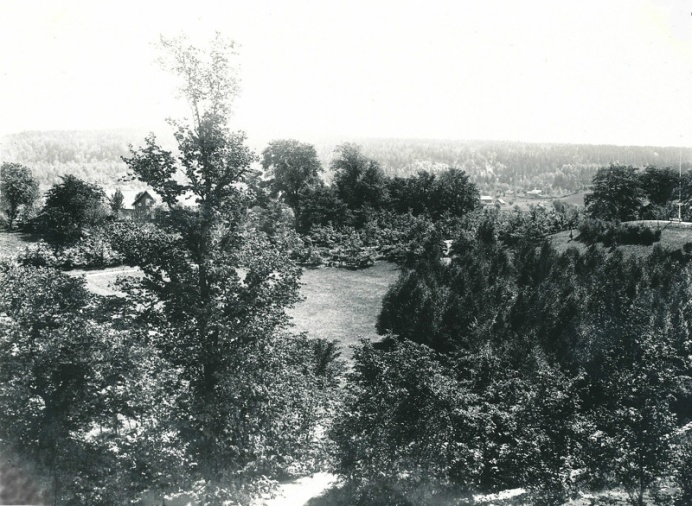 "The view of the church park in 1904. The picture showing the southeastern view was taken from the steeple. You get a good idea of how beautiful the park was in its ""infancy"". To the far right, the parks hill, flagpole and bench can be seen. By the path to the left, you can see the newly planted oak trees and in the foreground a young birch grove. To the left a glimpse of Sörgården and the house in front of the mountain is Bille mill and Vassbacken."