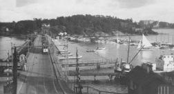 Den gamla Tranebergsbron med den ännu äldre flottbron med spårvagnen på väg över. Spårvägen invigdes 1914 och år 1917 startade Brommalinjen