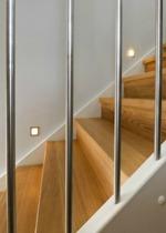 """Tät trappa med steg och sättsteg i mattlackad ek. Övrigt i vitmålad furu. Räcke """"Pop"""", med spjäla nr: 11 i rostfritt stål."""