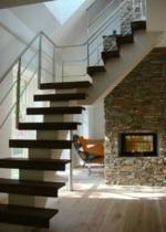 Balktrappa med vilplan och steg i oljad valnöt och vitmålad balk. Räcke 2 i rostfritt stål.