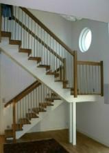 """Balktrappa med vilplan och steg i oljad ek och vitmålad balk. Räcke """"Bas"""", med spjäla nr: 11 i rostfritt stål."""