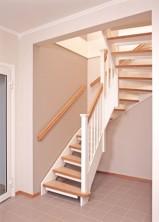 """Öppen U-trappa med steg belagda med linoleummatta och kantlister och handledare i klarlackad ek. Övrigt i vitmålad furu. Blocksteg. Räcke """"Classic"""", med profilerade stolphattar."""