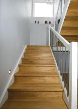 """Tät U-trappa med vilplan, steg och sättsteg i mattlackad ek. Övrigt i vitmålad furu. Räcke """"Pop"""", med spjäla nr: 11 i rostfritt stål."""