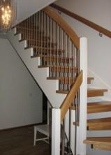 """Öppen L-trappa med plansteg och handledare i mattlackad ek. Övrigt vitmålas. Underliggande vangstycken. Räcke """"Pop"""", med spjäla nr: 4 i rostfritt stål."""