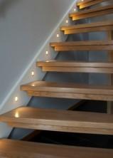 Öppen trappa. Plansteg i mattlackad ek, vangstycken vitmålade. Runda lampor i vangstycket.