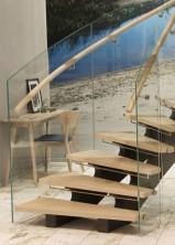 """Trappa av modell """"Serpentine"""" med laserade eksteg, balkar i täckmålat stål och svängt glas i räcke."""