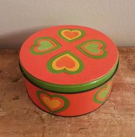 Rund orange burk med hjärtmotiv. Diam. 18 cm, höjd 8 cm. Liten buckla i locket, annars gott skick. 60 SEK