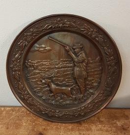 Väggtavla i brons (?) med jaktmotiv. Diam. 24,5 cm.