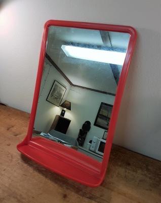 Spegel i röd plast med hylla. Höjd 37,5 cm och bredd 26 cm.  125 SEK