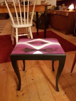 Svartmålad pall med omklädd sittdyna. Längd 41 cm, bredd 30,5 cm, höjd 43,5 cm (exkl. dyna) 250 SEK