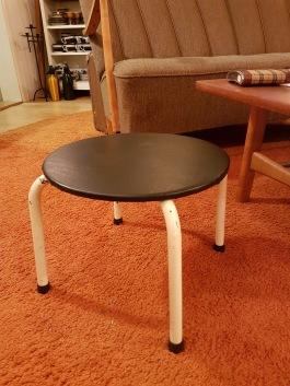 Liten låg pall med järnben och svartklädd sits. Höjd 27 cm, diam. 33 cm. 225 SEK