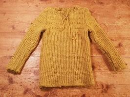 Handstickad tröja med knytband framtill. Senapsfärgad. För ca 2 år. Längd 40 cm, längd arm från axel 35,5 cm. Bredd (ej uttänjd) ca 23 cm. Ej använd. 80 SEK