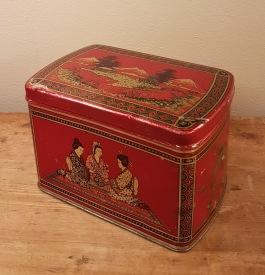 Röd burk med kinesiskt motiv. Längd 21 cm, bredd 13,5 cm. Höjd 13,5 cm. Lite skavmärken, annars gott bruksskick. 65 SEK