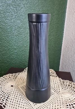 Hög svart mönstrad vas märkt AWF, Norge. Höjd 23 cm. Liten nagg vid foten, annars fint skick. 70 SEK