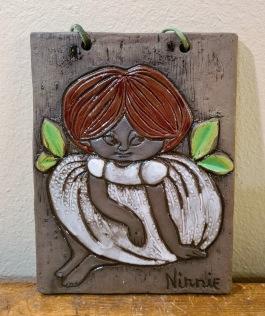 Keramiktavla Ninnie Keramik - flicka med brunt hår. Höjd 18 cm, bredd 13,5 cm. Fint skick. 75 SEK
