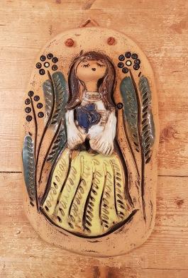 Keramiktavla med kvinnomotiv i relief. Höjd 33 cm, bredd 20 cm. Svårtydbar signatur på baksidan. 75 SEK