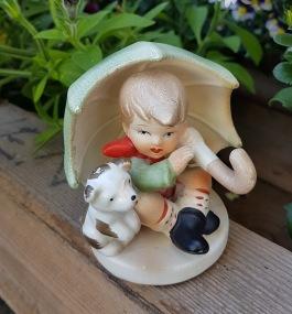 Figurin, sittande pojke med paraply. Höjd ca 8 cm. Fint skick. 40 SEK
