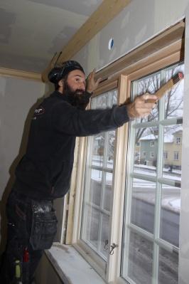Peter mäter fönstersmygar i en villa i Enskede.