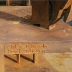 Här kan vi se den lilla anläggningsytan som bär upp skulpturen. Texten som kan ses i bordet är vattenskuren. Texten är en dikt av Stig Järrel för Nils Ferlin.