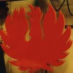 Fågeln pulverlackas i rött och orange. Plåtarna är förskjutna för att få brandkänslan, belysningsarmaturen monters i centrum av skulpturen får att lysa upp mellan eldsflammorna.