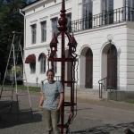 Konstnären med skulpturen monterad på plats.