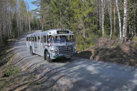 Veteranbuss från 1950-talet på väg med besökare till bilkyrkogården.