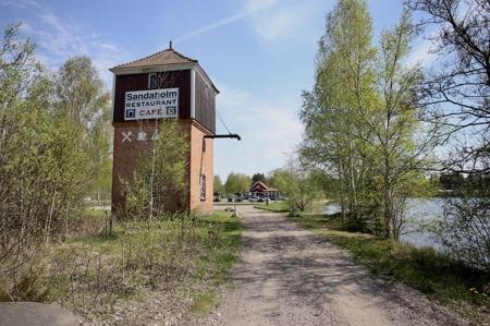 Stationsbyggnaden vid Sandaholm är nu Vägkrog. Strax intill finns det gamla vattentornet där ångloken fyllde på vatten.