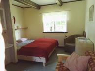 Rum 6 Harebo. Rummet har en dubbelsäng och en bädsoffa, en hylla, ett litet bord, handfat och klädhängare. Passar familj 2 vuxna och 1 eller 2 barn.