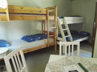 Room 8, Skallebo. A family room for up to 5 people. It includes 2 bunk beds, table and chairs and a sink.