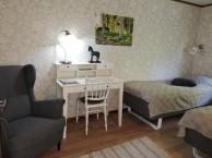 Zimmer 5, Mundekulla. Das gemütliche Zimmer hat 2 Einzelbetten, einen kleinen Tisch, Stuhl, einen Sessel, Kleiderschrank und Waschbecken.