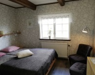 Room 6, Harebo. The room has a double bed and a sofa bed, a shelf, a small table, a sink and clothes hangers. Suitable for a family of 2 adults and 1 or 2 children.