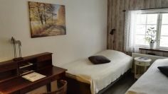 Room 7, Bredalycke. The room is outfitted with two beds, dest, sitting area with 2 arm chairs and a sink.