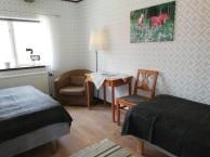 Zimmer 10, Studsmåla. In diesem Zimmer befindet sich ein Doppelbett und ein Einzelbett,  ein kleiner Tisch mit 2 Stühlen und ein Waschbecken. Hier sind Hunde ebenfalls willkommen!