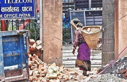 Kvinna bär sten, efter jordbävningen, Kathmandu, Nepal
