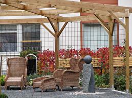 De mysiga korgstolarna bidrar mycket till det varma och inbjudande intrycket under pergolans tak.