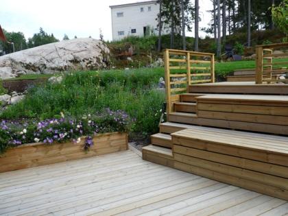 På berghällen bakom huset byggdes en platå upp. En trappa, som planerats för att också kunnaanvändas som sittplats och förvaring, leder upp till platån dit familjen gärna slår sig ner och njuter av det fina kvällsljuset, utsikten över trädgården och omgivningarna.