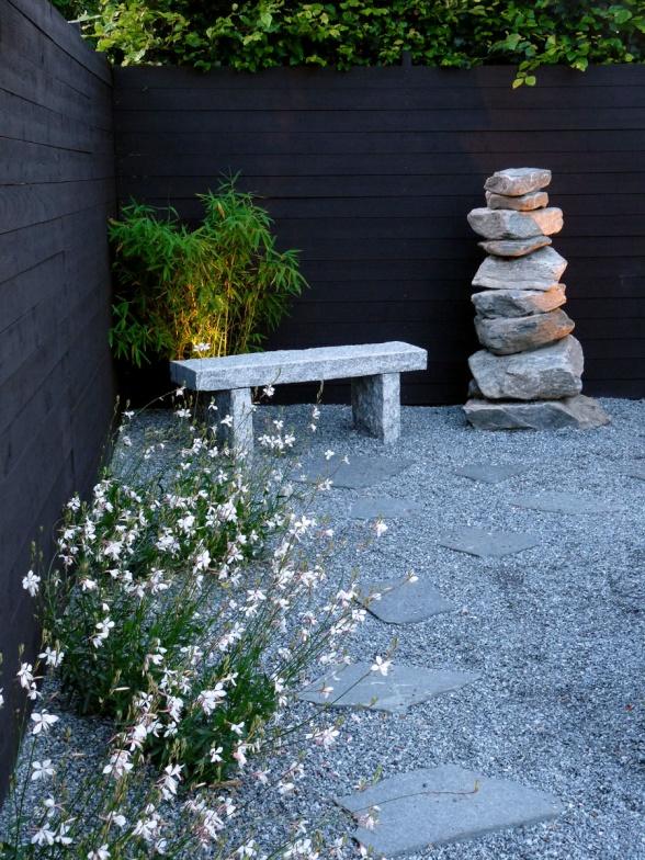 Här några stenblock staplade till en bänk längst in i hörnet och stenstapeln intill blir ett konstverk och ett blickfång. En bambu med belysning bakom passar fint in i sammanhanget. Det svartmålade planket gör att både sten och grönska framträder tydligare. Grus och oregelbundna trampstenar fullföljer det japanska temat.