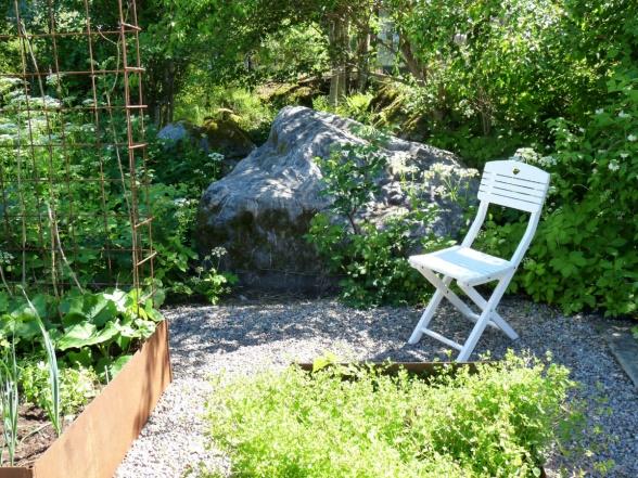 En liten stol placerad så att man lätt kan sätta sig en stund och njuta av grönsaksodlingarna.