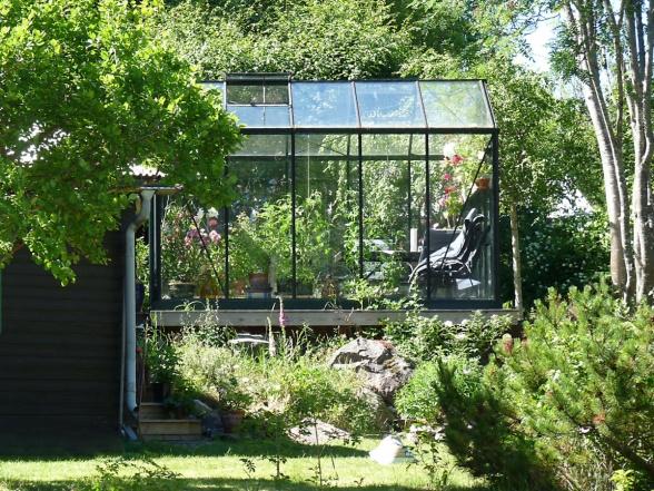 Ett vackert växthus med annorlunda, upphöjd placering. Här finns plats för en skön stol - och för växter förstås.